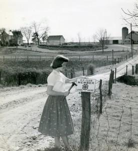 Girl Hangs 4-H Sign