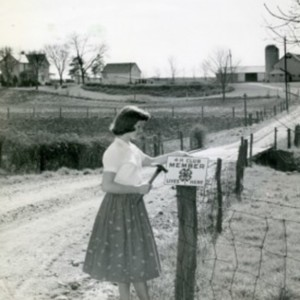 Girl Hangs 4-H Sign.jpg